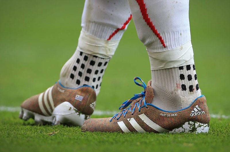 Quấn băng keo thể thao ở phần nối giữa tất ống chân và tất đá bóng lửng